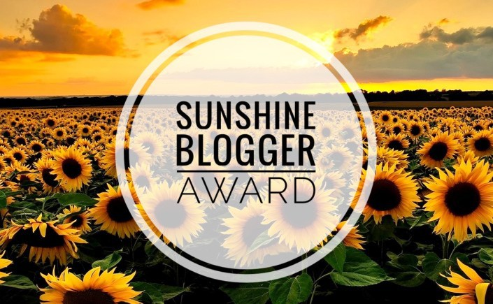 Sunshine Blogger Award logo of field of sunflowers with sunset in background
